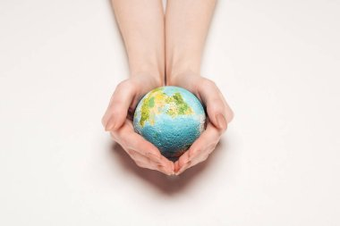 Cropped view of woman holding globe model on white background, global warming concept stock vector