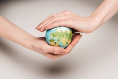 partial view of woman holding earth model on white background, global warming concept