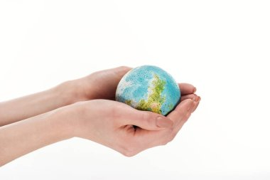 partial view of female hands with globe model isolated on white, global warming concept