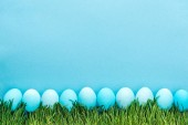 top view of traditional easter eggs on grass isolated on blue