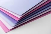 Fotografie leere blaue, weiße, rosa und lila Blätter Papier auf weißem Hintergrund
