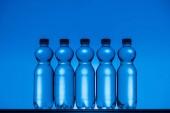 Fotografia tonica immagine di plastica bottiglie di acqua su priorità bassa al neon blu con retroilluminazione