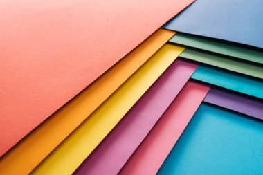 flat lay of blue, orange, green, burgundy, yellow, pink and purple sheets of paper