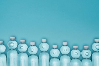 top view of plastic water bottles isolated on turquoise with copy space