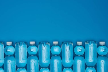 top view of arranged plastic water bottles isolated on blue with copy space