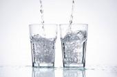 Wasser in Gläsern auf weißem Hintergrund mit Hintergrundbeleuchtung und Spritzern