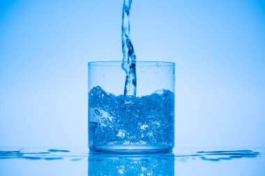 toned image of water pouring in drinking glass on blue background with splashes