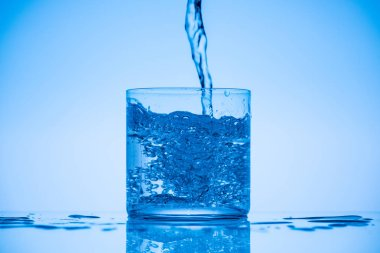 toned image of water pouring in glass on blue background with splashes and copy space
