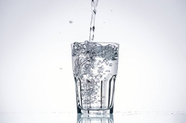 Water pouring in drinking glass on white background with backlit and copy space stock vector