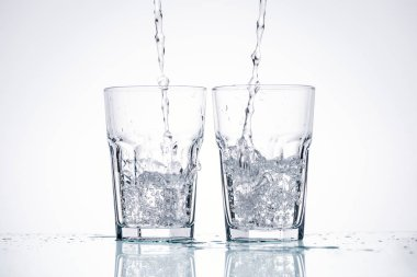 water pouring in glasses on white background with backlit