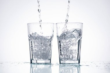Water pouring in glasses on white background with backlit and splashes stock vector