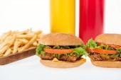 Fotografie Selektivní fokus chutné kuřecí Hamburgery, hranolky a láhve izolované na bílém
