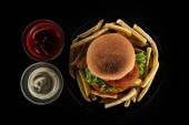 pohled shora chutné hranolky a burger kuřecí majonézou a kečupem, samostatný na černém