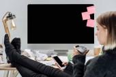 Selektivní fokus dívku sedící na nemravné pracovišti s thermomug a pomocí smartphone izolované Grey