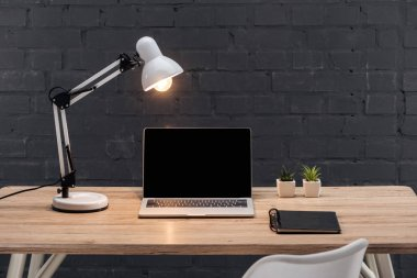 Modern workplace with laptop with blank screen, plants, bright lamp and notebook on wooden table near black brick wall stock vector