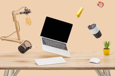 Laptop with blank screen and stationery levitating in air at workplace isolated on beige stock vector