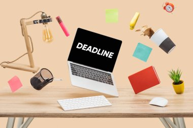 laptop with deadline lettering on screen, thermomug with coffee splash and stationery levitating in air above wooden desk isolated on beige
