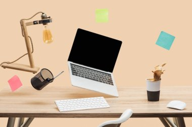 laptop with blank screen, lamp, empty sticky notes and stationery levitating in air above wooden desk with thermomug with coffee splash isolated on beige