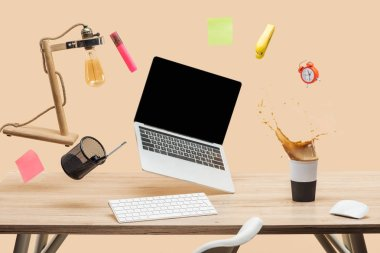 laptop with blank screen, lamp, empty sticky notes and stationery levitating in air above workplace with thermomug with coffee splash  on table isolated on beige