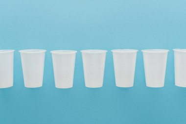 Flat lay with white plastic cups isolated on blue with copy space stock vector