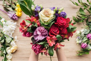 Partial view of florist holding bouquet of fresh flowers on wooden surface