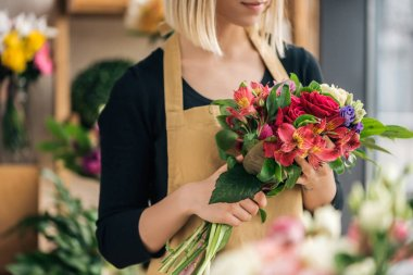 Cropped view of florist in apron holding bouquet in flower shop stock vector