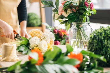 Cropped view of florist cutting off flower stalks with pruning shears
