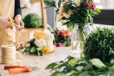 Partial view of florist making bouquet in flower shop