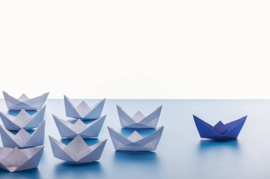 Paper boats on light blue surface on white background stock vector