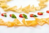 selektivní zaměření chutných nachos a chilli papriček s bazalkou na bílém pozadí