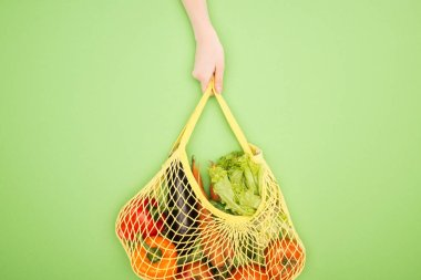 partial view of woman holding string bag with whole vegetables on light green