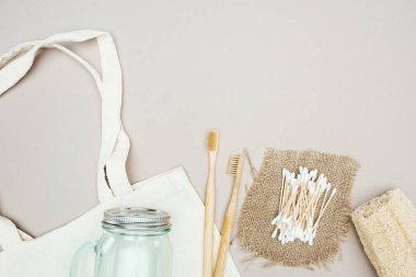 wooden toothbrushes, organic loofah, cotton swabs, sackcloth, glass jar and white cotton bag