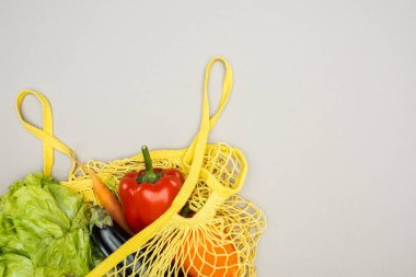 yellow string bag with fresh ripe vegetables on grey background