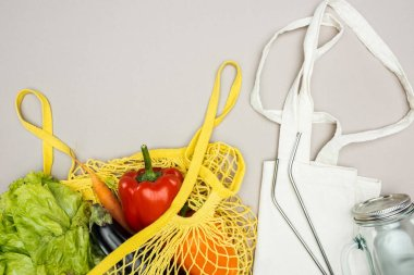 yellow string bag with fresh ripe vegetables, metal straws, glass jar and cotton bag on grey background