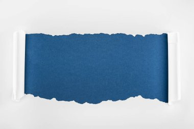 ragged textured white paper with curl edges on deep blue background
