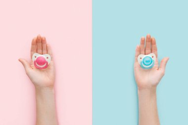 partial view of women holding pacifiers on blue and pink background with copy space