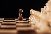 messa a fuoco selettiva della scacchiera di legno con figure di scacchi e pedone di fronte isolato sul nero