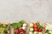 Pohled shora toasty s pokrájenou zeleninu a parmskou šunkou na texturou povrchu