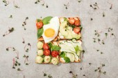Pohled shora toasty s zelenina, sázené vejce, bazalka ang řeřicha setá na texturou povrchu