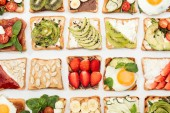 Top view of toasts with cut fruits, vegetables and peanuts on white