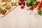 pohled shora na toasty se zeleninou a šunkou na dřevěný stůl s přísadami