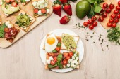 pohled shora složek a toasty se zeleninou, vejcem a parmskou šunkou na dřevěný stůl