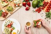 pohled shora ženy držící šálek kávy u stolu s ingrediencí, zelení a toasty se zeleninou a šunkou