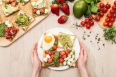 Fotografie top view of woman holding plate with vegetable toasts on wooden table with greenery and ingredients