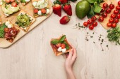 top view of woman with delicious vegetable toasts and fresh ingredients on wooden table
