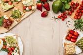 Fényképek felülnézete a fából készült asztal pirítós zöldségek, gyümölcsök és prosciutto növényekkel és összetevők