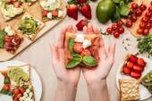 Selektivní fokus ženy držící toast s cherry rajčaty a parmskou šunkou dřevěný stůl s zelení a ingredience