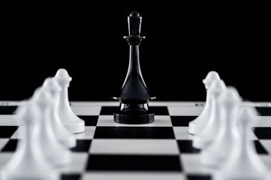 selective focus of chessboard with black queen figure among white pawns isolated on black