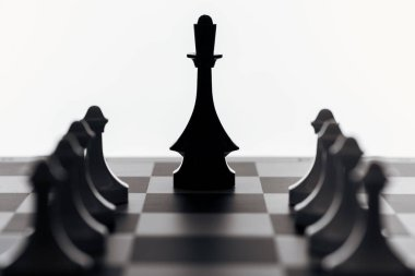 selective focus of chessboard with black queen and pawns isolated on white