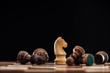 selective focus of chessboard with scattered wooden figures and knight isolated on black